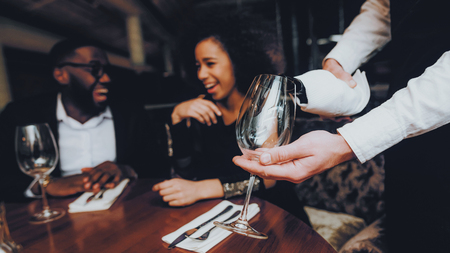 Foto de Waiter Pouring Wine to Glass Couple in Restaurant. Romantic African American Couple in Love Dating. Cheerful Man and Woman Drinking Red Wine. Romantic Concept. Anniversary. Bottle of Red Wine. - Imagen libre de derechos