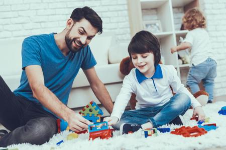 Foto de Father and Eldest Sons is Playing with Toys on Carpet. - Imagen libre de derechos