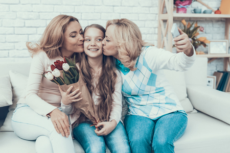 Happy Family Taking Selfie on Daughter\'s Birthday. Happy Family. Mother with Daughter. Smiling Women. Smiling Grandmother. Celebration Concept. Using Smartphone. Taking Photo. Bouquet in Hands.