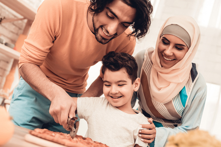Foto de Happy Arabian Family Eating Pizza in Kitchen. Muslim Family. Smiling Boy. Young Arabian Woman. Modern Kitchen at Home. Man Using Kitchenware. Young Family. Wooden Table in Kitchen. Food on Table. - Imagen libre de derechos