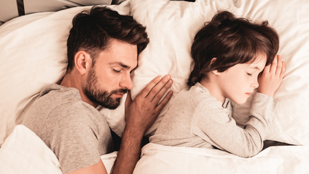 Little Son with Tired Sleeping Father in Bed. Family in Morning. Happy Family Concept. White Bed in Room. Father and Son at Home. Morning Routine. Lying in Bed. Sleeping Man. Blanket and Pillows.