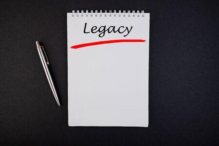 Photo pour Legacy text, inscription, phrase is written in a notebook that lies on a dark table and a pen. Business concept. - image libre de droit