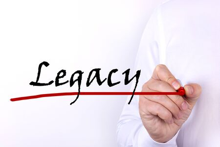 Photo pour A person writes text, a word, the phrase Legacy with marker on a light background. Business concept. - image libre de droit