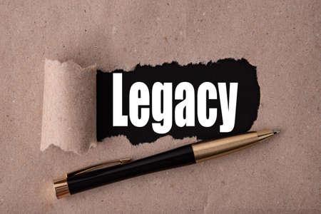 Photo pour LEGACY text written under torn paper and a recumbent metal pen. Business strategy concepts. - image libre de droit