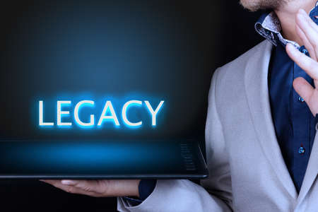 Photo pour Businessman, man holds in his hand a tablet with a neon word, LEGACY text. Business concept. - image libre de droit