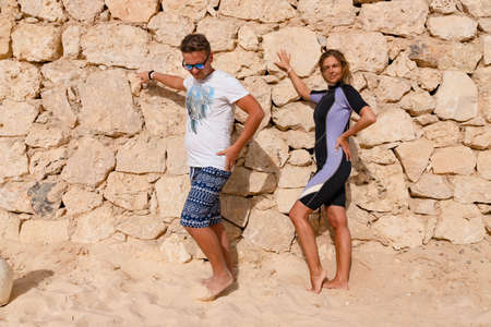 Photo pour A blonde, a beautiful girl in a wetsuit and a guy are posing on a sunny day, on the shore against the background of a stone wall. - image libre de droit