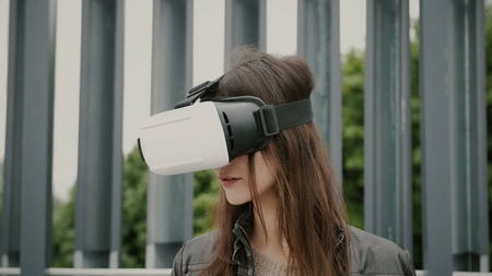 Brunette woman uses virtual reality glasses in the urban space. 4k