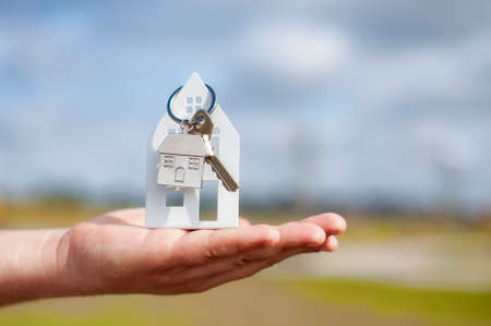 Photo pour Guy holds the house keys in his hands against the background of clouds. Concept on the topic of buying a new home - image libre de droit