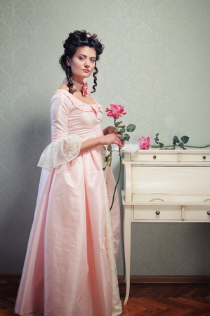 A young brunette lady in a pink ancient dress holding a rose