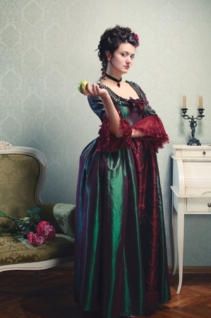 Beautiful brunette in a historical dress posing with an apple in her hand