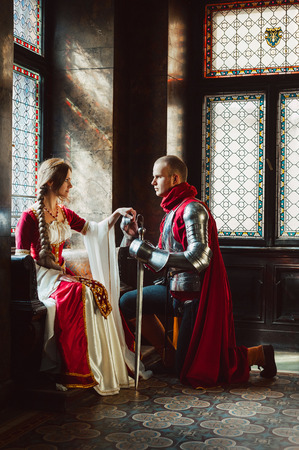 A young knight kneels down before his lady to pronounce his engagement vow.