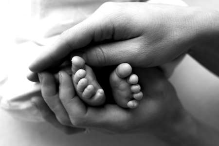 Photo for Feet of a newborn in the hands of a father, parent. Studio photography, black and white. Happy family concept. - Royalty Free Image