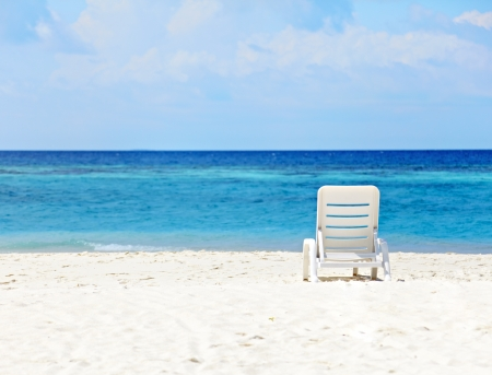 White  deck-chair standing on the beach at the blue ocean