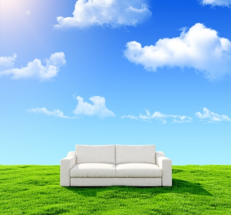 White sofa on a green field against the blue sky