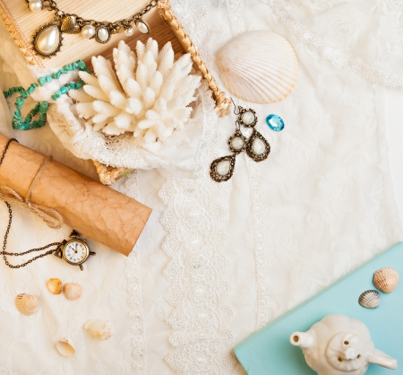 Vintage background with seashells, paper scroll, watch and jewelry. Romantic photo
