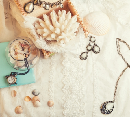 Vintage background with seashells, watch and jewelry. Romantic photo