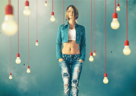 Photo pour Young woman in a trendy clothes stand between lightbulbs  Unusual art image - image libre de droit