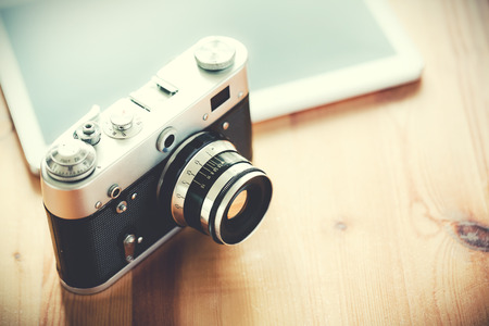 Photo for Old vintage camera with a tablet on a wooden table. - Royalty Free Image