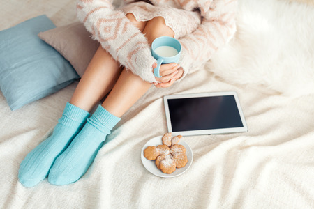 Soft photo of woman on the bed with tablet and cup of milk in hands, top view point