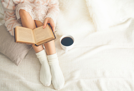 Soft photo of woman on the bed with old book and cup of coffee, top view point