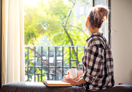 Photo for Young pretty woman  sitting at opened window drinking coffee and looking outside enjoys of rest - Royalty Free Image
