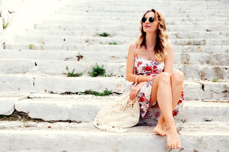 Photo pour Beauty tanned and stylish young woman in dress sitting on steps in sunny bright summer day. Travel and vacation concept. - image libre de droit