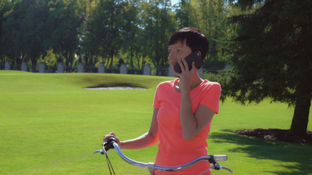 Caucasian happy woman rides bike outdoors. Smiling brunette talking with friend by phone. Active lifestyle in sunny day. Cheerful girl answer call in park summertime. Women wearing casual bright color t-shirt.