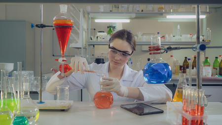 Adult doctor working in microbiological or chemistry or medical laboratory. pouring liquid to glass bulb. Happy caucasian woman looking at the camera with smile wearing in white coat and eyeglasses working alone in lab.