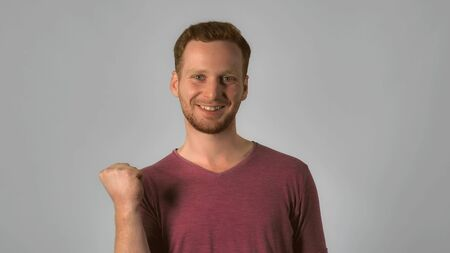 Photo for happy caucasian guy with red hair celebrate success. handsome redheaded men wearing in casual t-shirt. Portrait ginger young caucasian man on grey background - Royalty Free Image