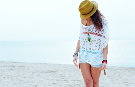 Young woman in stylish outfit walking on the the beach