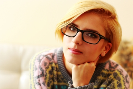 Closeup portrait of a young blonde woman in glasses