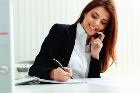 Young cheerful businesswoman talking on the phone and writing notes in office