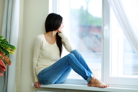 Photo for Young happy woman sitting on a window-sill and looking outside - Royalty Free Image