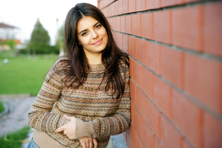 Beautiful happy woman standing near brick wall