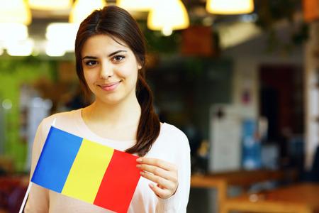 Photo pour Happy female student holding flag of Romania - image libre de droit