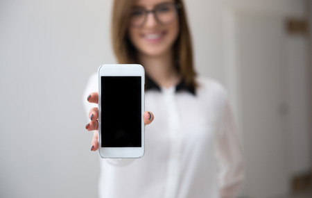 Businesswoman showing a blank smartphone screen. Focus on smartphone