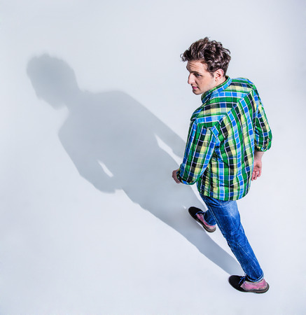 Top view portrait of a young man in colourful wear walking  over gray backgorund