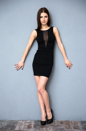 Full length portrait of a cute woman in hot dress leaning on the wall