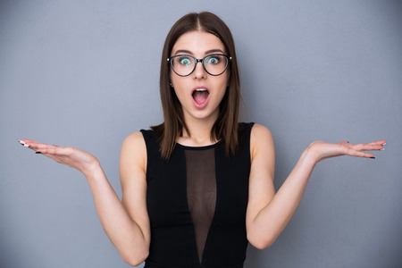 Young beautiful woman with facial expression of surprise standing over gray background. Wearing in trendy black dress and glasses. Looking at the cameraの写真素材