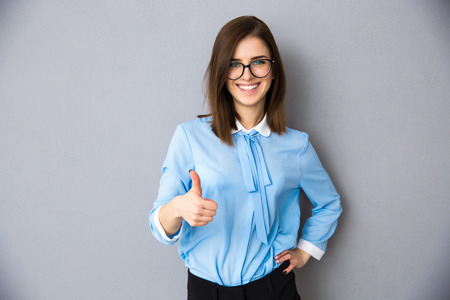 Happy businesswoman showing thumb up over gray background. Wearing in blue shirt and glasses. Looking at camera