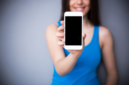 Happy woman showing blank smartphone screen over gray background. Focus on smartphone.