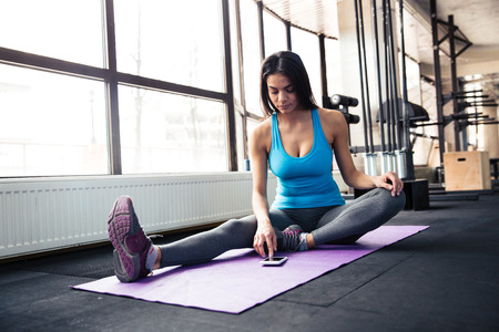 Young woman sitting on yoga mat and using smartphone at gym