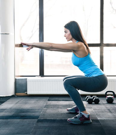 Photo for Side view portrait of a young woman doing squats at fitness gym - Royalty Free Image