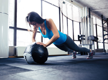 Young woman doing push up on fit ball at gym