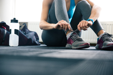 Woman tying shoelaces at gym