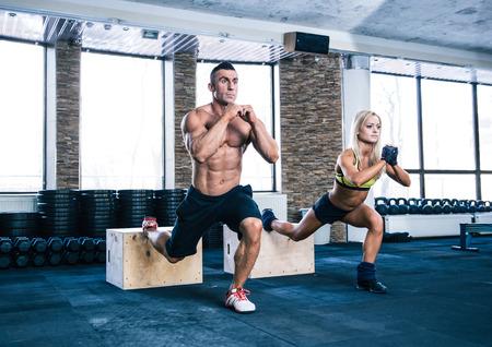 Foto de Woman and man working out with fit box at gym - Imagen libre de derechos