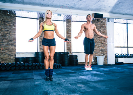 Muscular man and beautiful sporty woman workout with jumping rope in crossfit gym