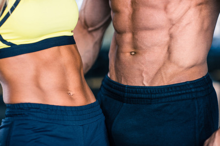 Closeup image of a muscular man's and sporty woman's torso