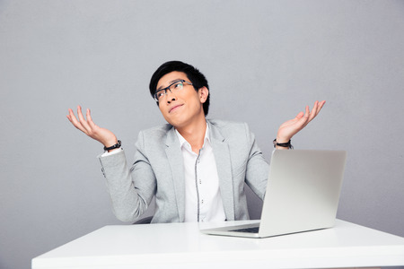 Young businessman sitting at the table with laptop and shrugging over gray background. I dont know.