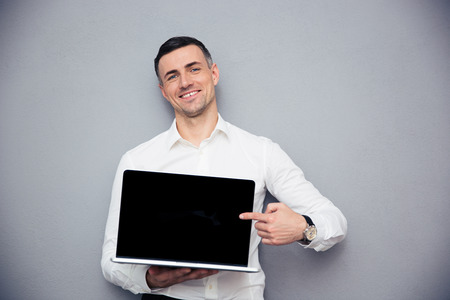 Photo pour Smiling businessman pointing finger on blank laptop screen over gray background. Looking at camera - image libre de droit